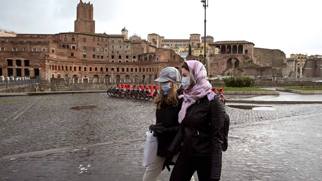 Two women wearing protective masks walks past the Trajan Forum in Rome on March 3, 2020