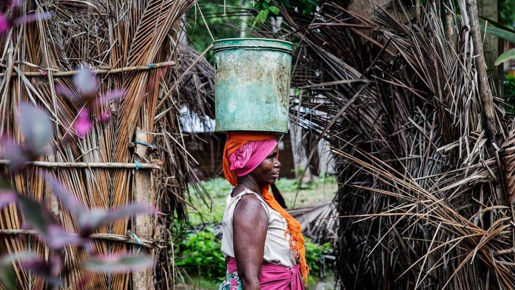 This picture taken on April 29, 2019 shows a woman carrying a bucket containing water collected from the Haikata well which was built in 1545 by African slaves and never been dried since then in Mikindani, southern Tanzania
