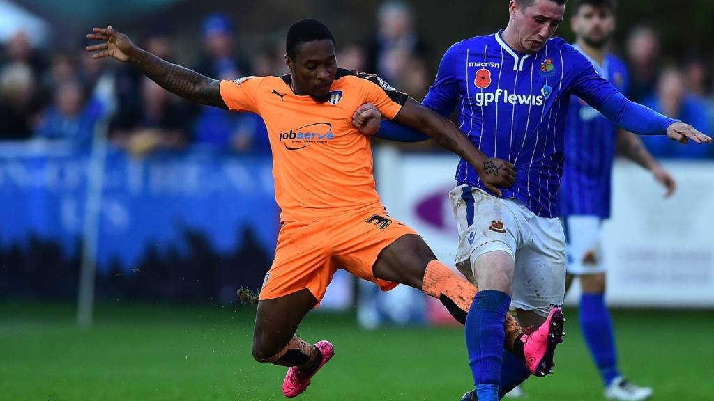 Michael Corcoran of Wealdstone is tackled by Callum Harriott of Colchester