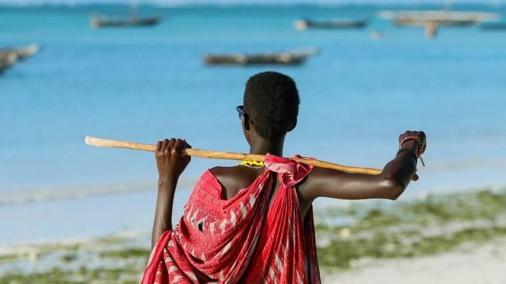 A Maasai tribesman stands on ocean coast in Zanzibar, Tanzania on August 20, 2018.