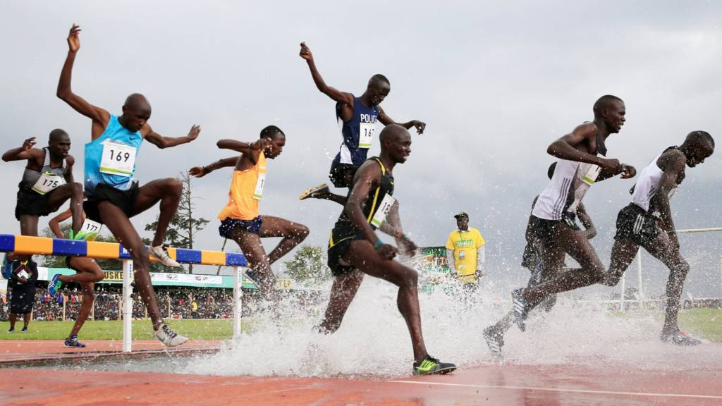 Athletes jumping over a hurdle