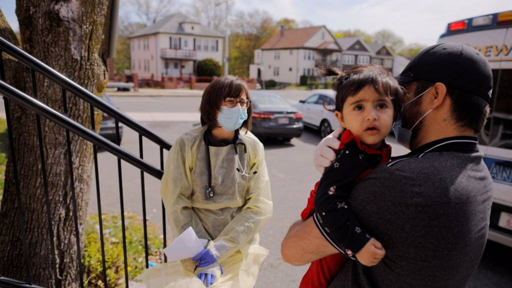 Syed Kamal holds his one year-old daughter Fareeha outside their home as Boston Medical Center pediatrician Dr. Sara Stulac does a routine check-up in an effort to use an ambulance to bring routine care and scheduled vaccinations to children amid the coronavirus disease (COVID-19) outbreak in Boston, Massachusetts, U.S., 8 May 2020