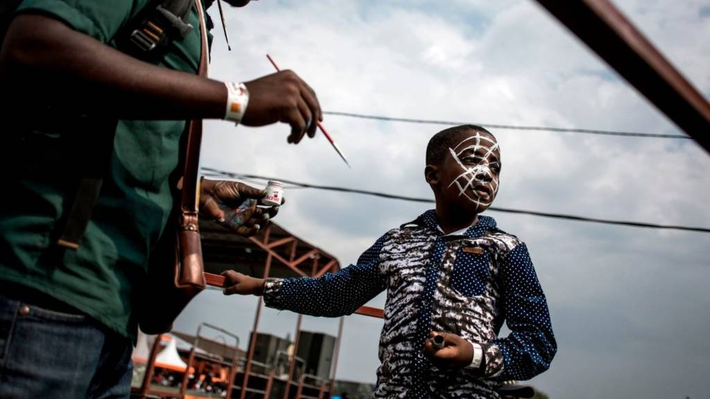 A young Congolese festival-goer gets his face painted during the Amani Festival