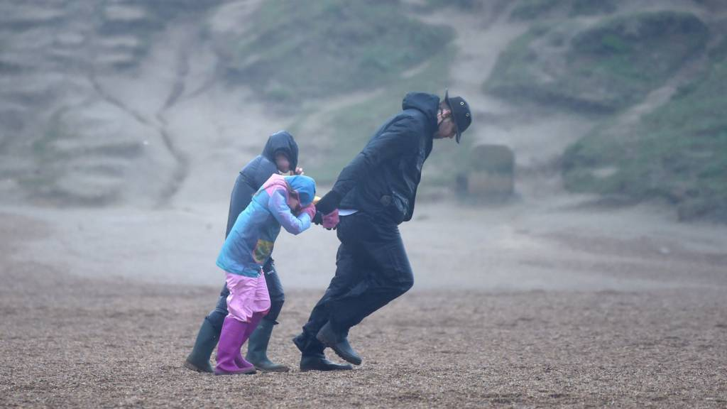 A man and children walk against the wind as Storm Ciara arrive