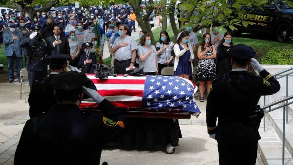 """Glen Ridge Police Department officer Charles Roberts""""s casket is saluted by fellow officers as his family looks on at his funeral service after the 45-year-old father of three died of the coronavirus disease (COVID-19) in Glen Ridge, New Jersey, U.S., May 14,"""