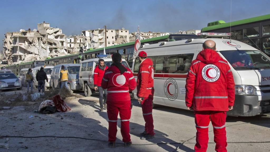 Syrian Arab Red Crescent workers stand next to buses and ambulances being used to evacuate civilians from rebel-held eastern Aleppo (15 December 2016)