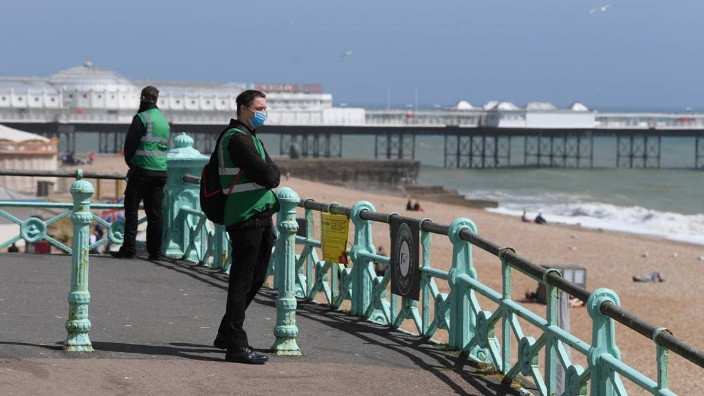 Local council stewards are positioned at the entrance of Brighton beach to try to control numbers