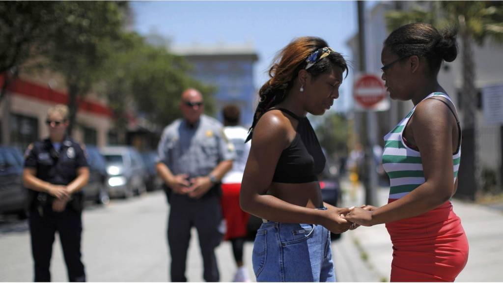 Mourners hold hands in Charleston