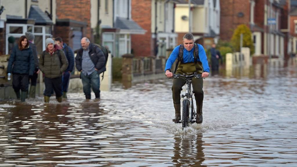 Man rides bike through floodwater