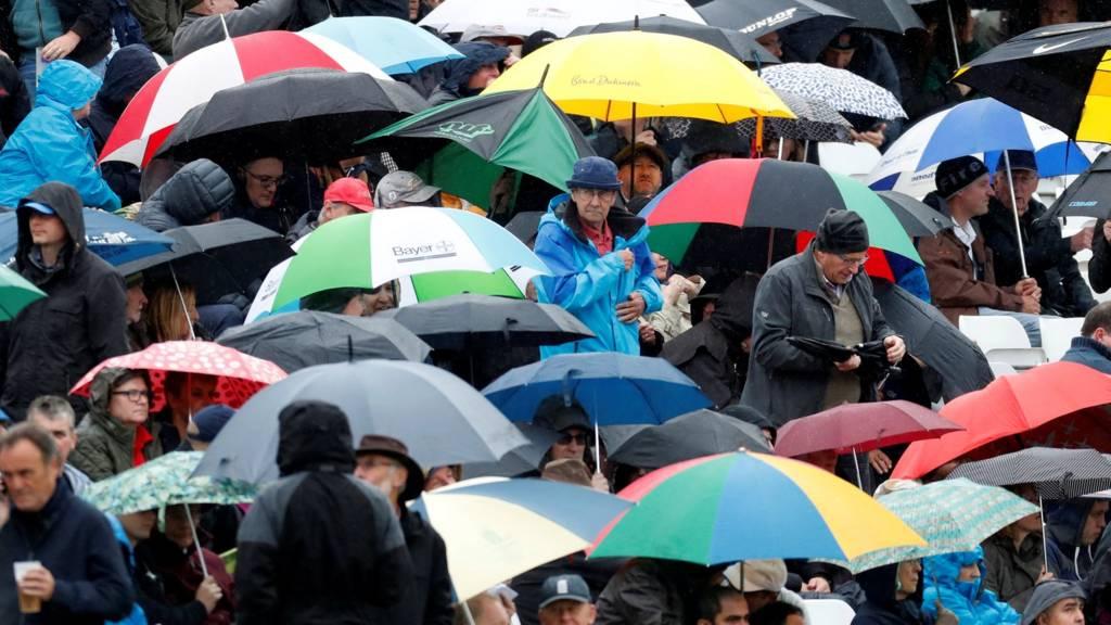 Fans shelter under their umbrellas