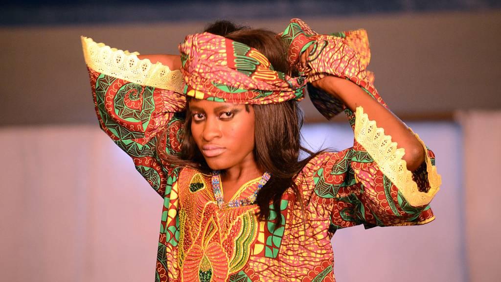A model in Kinshasa, DR Congo tying a head wrap