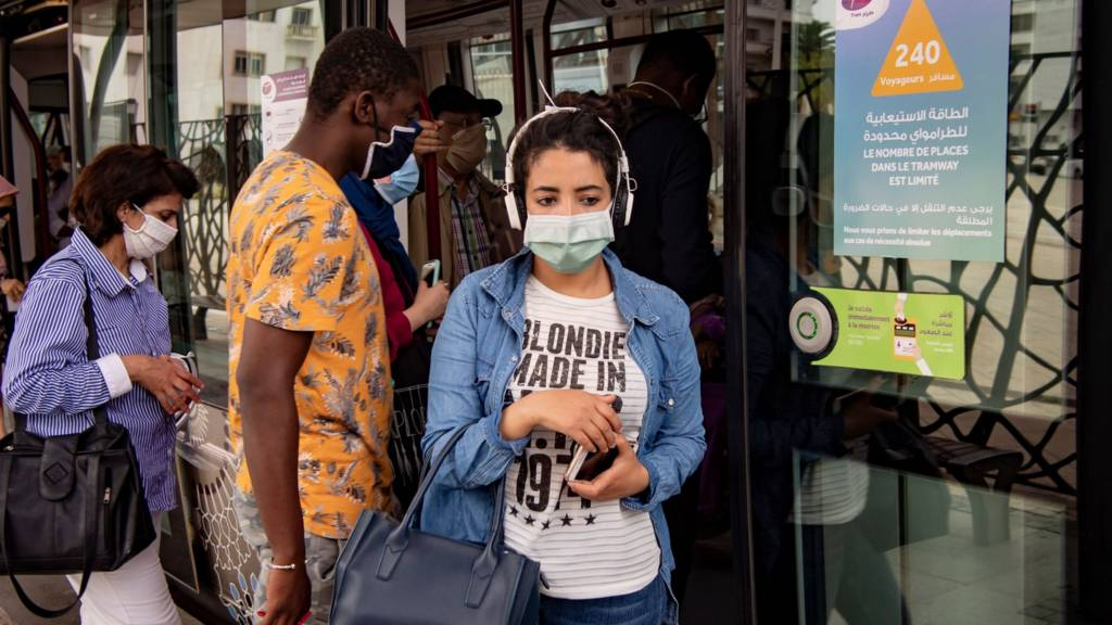 A woman wearing a protective mask steps off a tram in the center of the Moroccan capital Rabat on June 16, 2020.