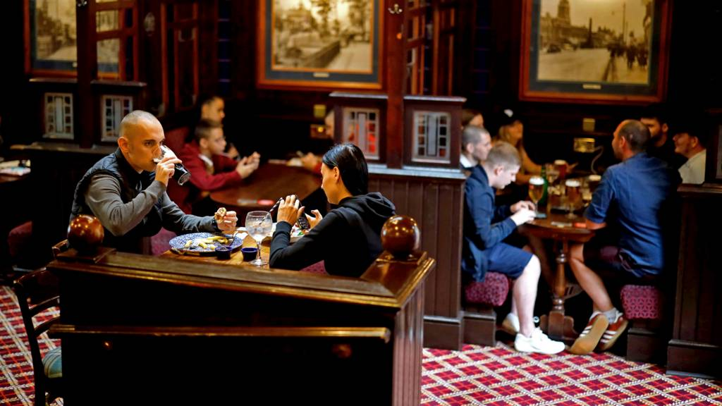 Customers sit in a pub