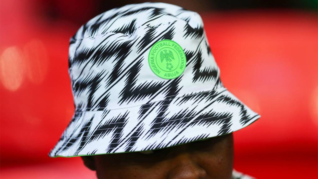 A Nigeria football fan wears the hat from the World Cup kit