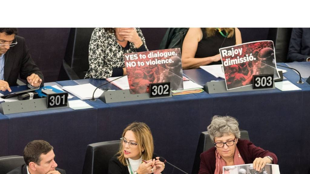 MEPs sitting with signs in front of their seats in the European Parliament