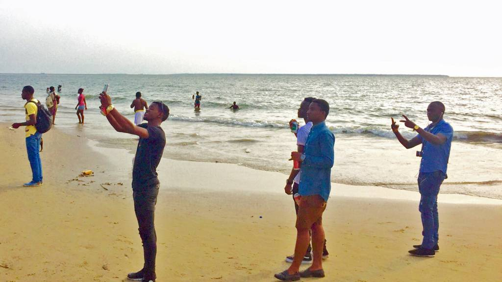 Men taking selfies on a beach in Gabon