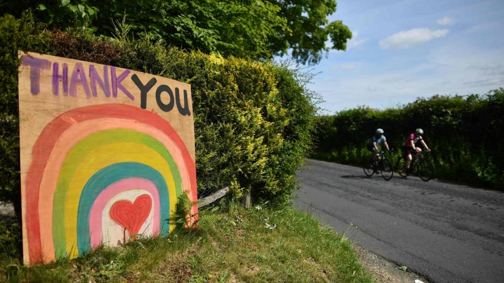 Cyclists ride past a sign thanking NHS staff that continue to work during the coronavirus pandemic near the village of Frant, southern England o