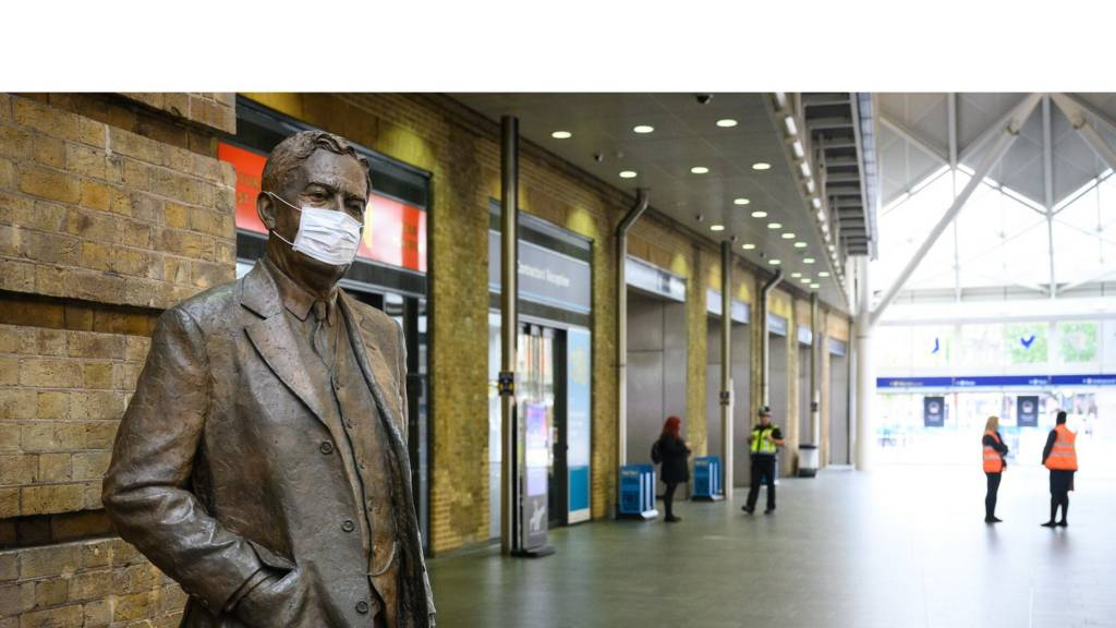 A protective face mask is seen on a statue of Nigel Gresley, the Chief Mechanical Engineer for the Great Northern Railway and the London ^ North Eastern Railway with Kings Cross station, on June 08