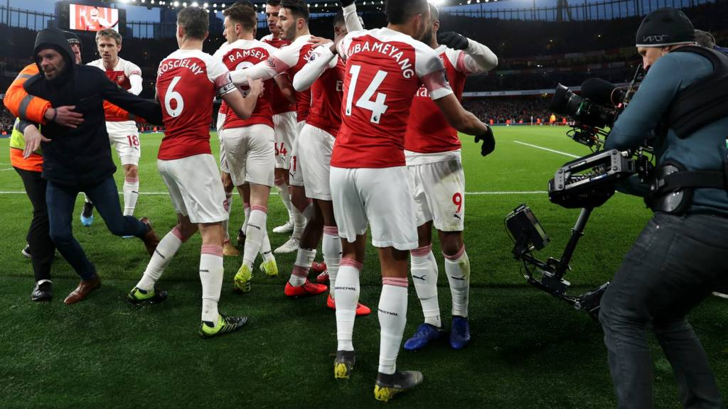 Arsenal celebrate as a spectator runs on the pitch