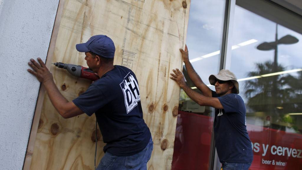 People board up windows of a business in preparation for the anticipated arrival of Hurricane Maria in San Juan, Puerto Rico on September 18, 2017