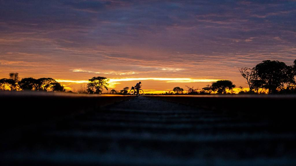 A man on a bicycle at the sun rise or set in Bulawayo, Zimbabwe