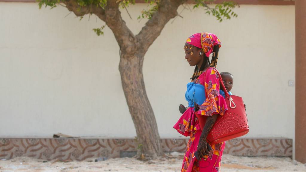 A woman walking with her baby in Nouakchott, Mauritania - 14 August 2019