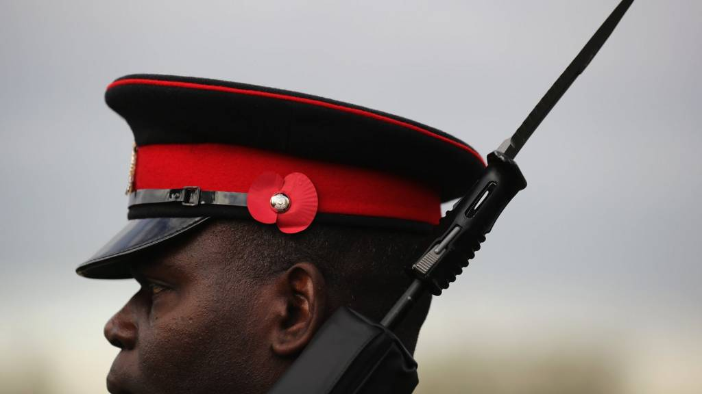 A soldier prepares for The Armistice Day Service at The National Memorial Arboretum on November 11, 2016