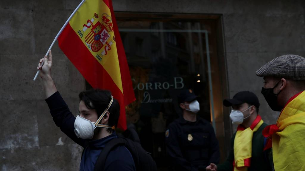 A man wearing a protective face mask carries a Spanish flag during a protest against the Spanish government's handling of the coronavirus disease in Madrid, Spain May 16, 2020