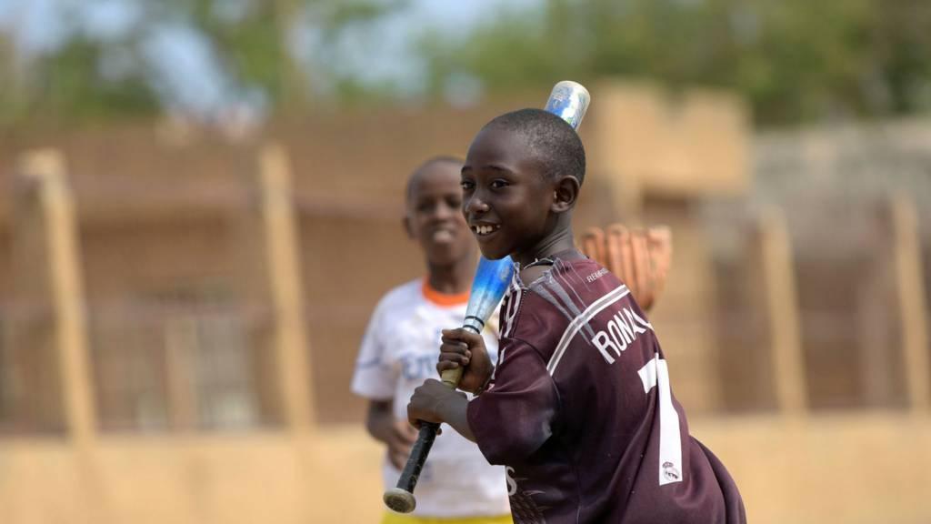 Senegalese boy playing baseball