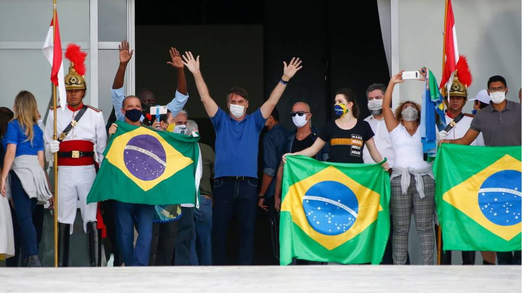 Jair Bolsonaro waving in mask with Brazilian flags