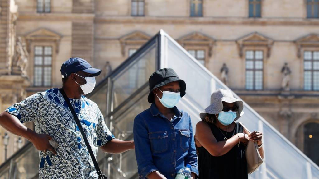 People wearing protective masks walk near the Louvre Museum as France reinforces mask-wearing as part of efforts to curb a resurgence of the coronavirus disease (COVID-19) across the country, in Paris, France August 6, 2020