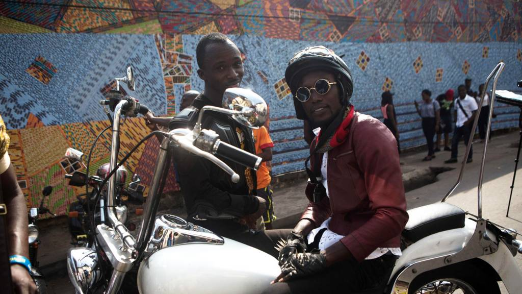 Two men sit and stand by a motorbike as they attend the Chale Wote street art festival in Accra, on 21 August 2016