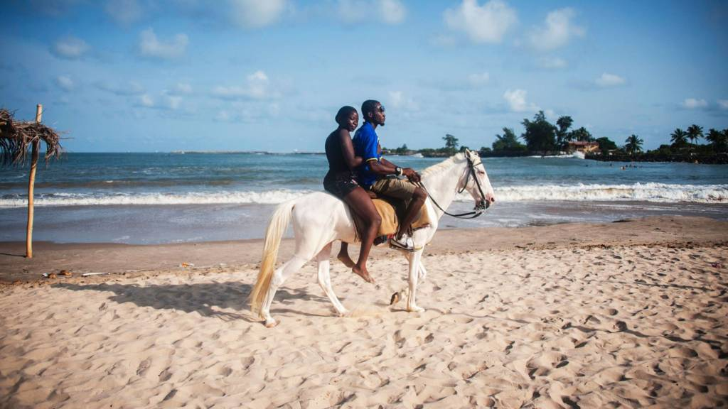 People riding a horse on a beach in Lagos, Nigeria