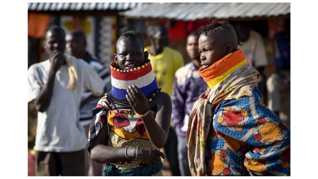 Women in elaborate neck adornements from the local Turkana community look on at Kalobeyei refugee settlement scheme in Kakuma