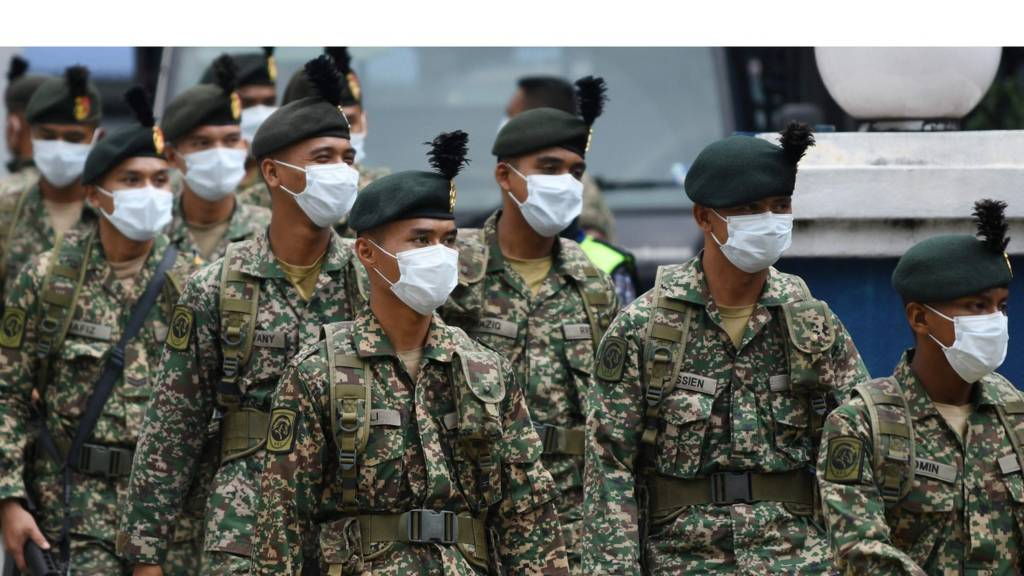 Soldiers wearing facemasks leave a police station to be deployed to man roadblocks during the control of movement in Kuala Lumpur on March 22, 202