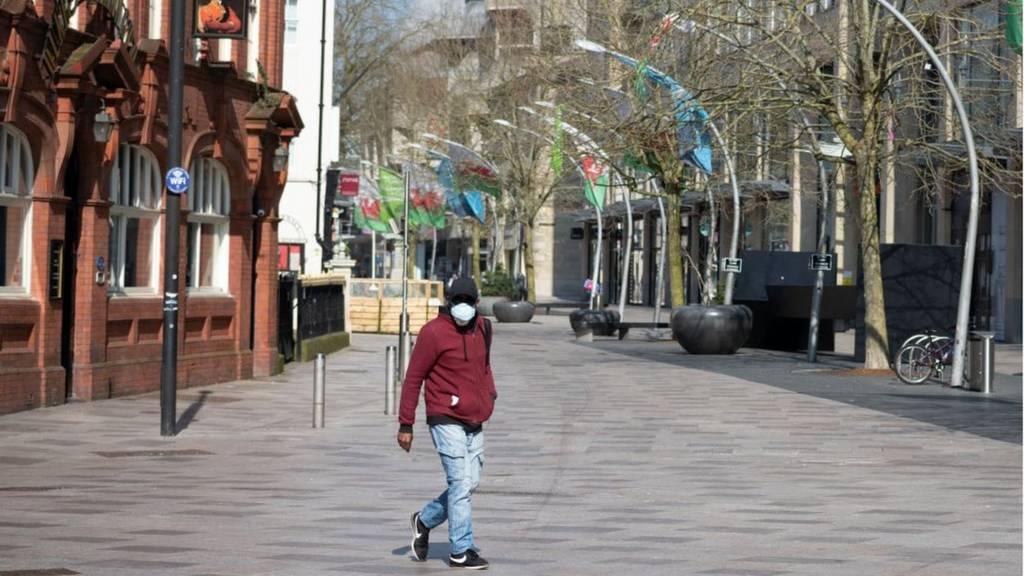 A man in a mask walking through Cardiff