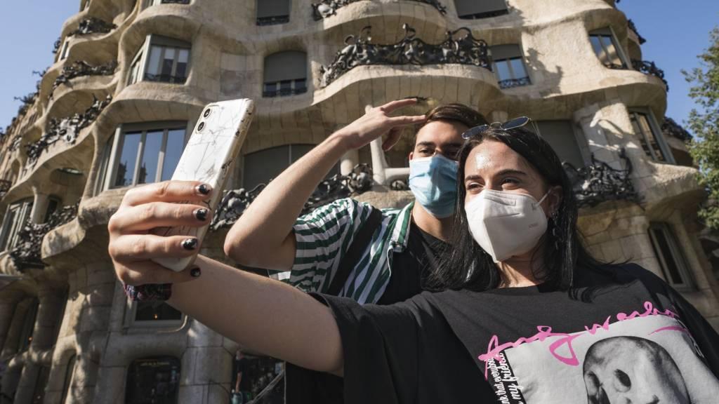 People pose for selfies in Barcelona, Spain, 27 July 2020