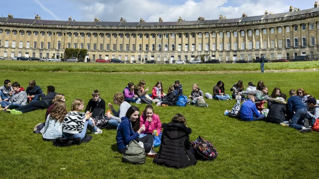 People picnic on the grass in front of the Royal Crescent, Bath