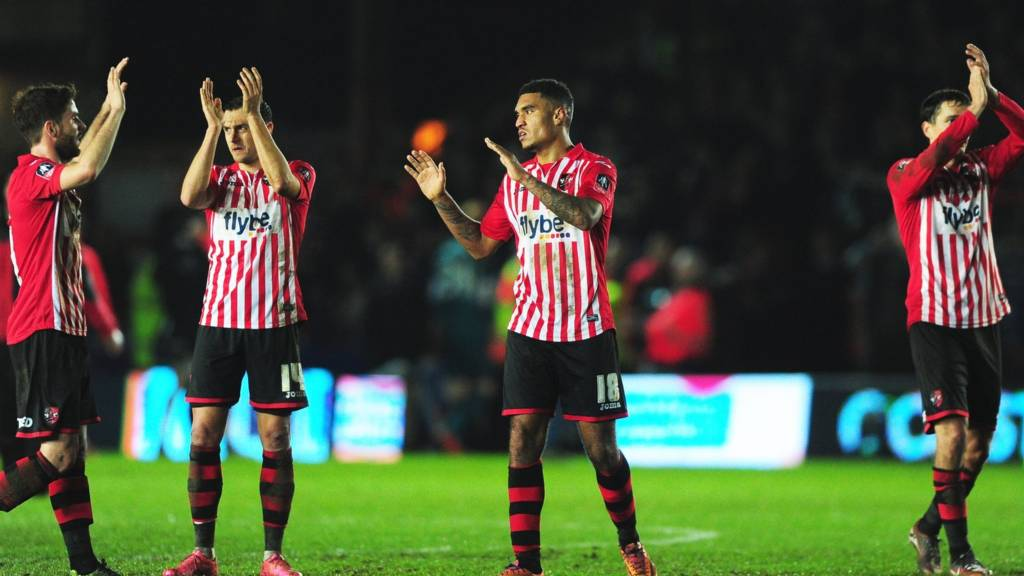 Exeter City players applaud the fans