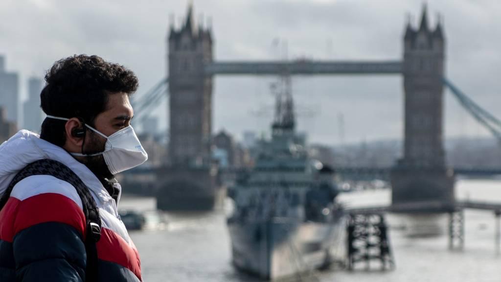 Man wearing a mask near Tower Bridge