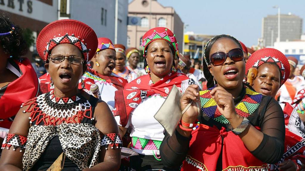 Hundreds of people adorned with traditional regalia march through the streets of Durban to celebrate Africa Day