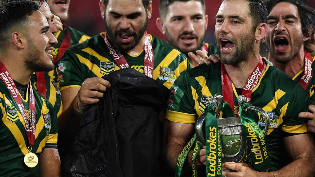 Cameron Smith (C) holds the trophy