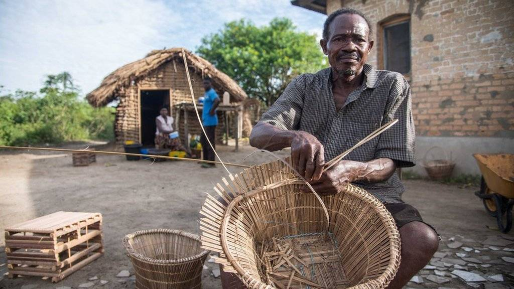 A palm nut cutter weaves in DR Congo