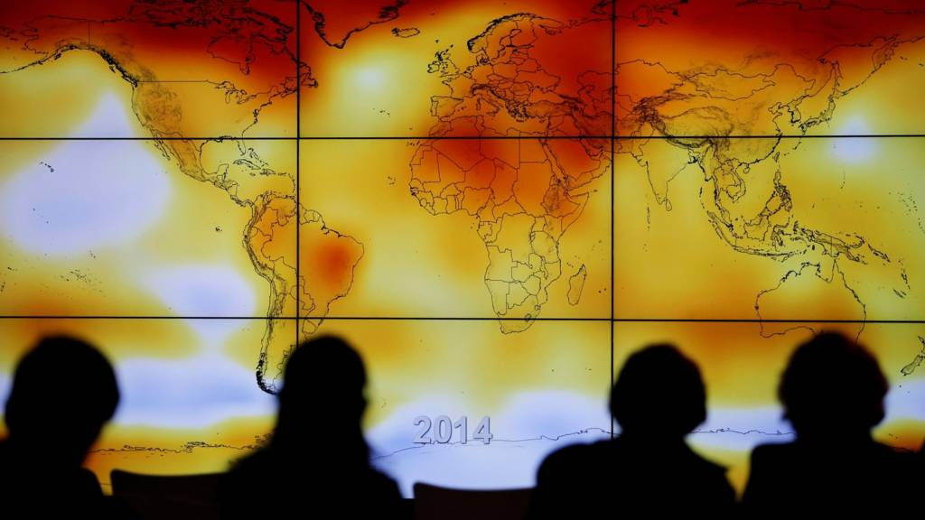 : Participants are seen in silhouette as they look at a screen showing a world map with climate anomalies during the World Climate Change Conference 2015