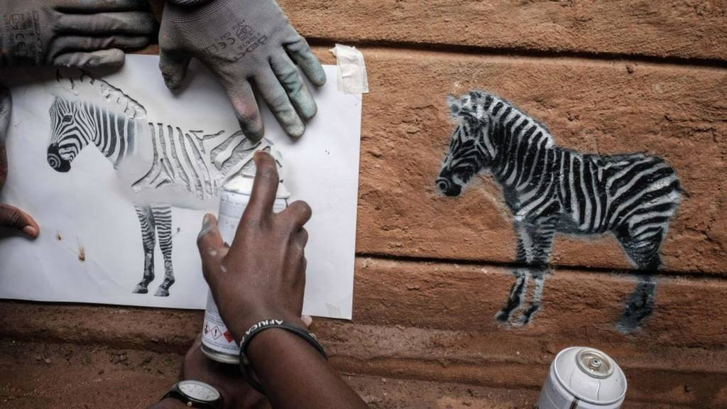 People stencil images of zebras in the Kibera neighbourhood of Nairobi, on April 25, 2018.