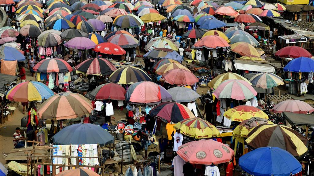 Traders cover their wares with umbrellas of different shapes and sizes along the railway line in Port Harcourt, Nigeria - February 2017