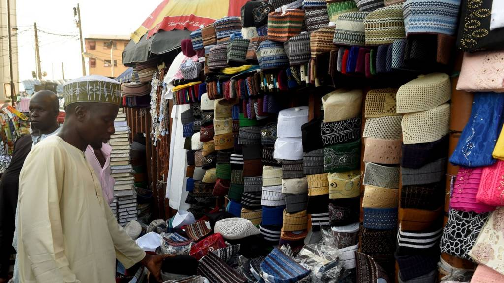 A man looks at various Taqiyah caps on sale in Lagos, on 26, 2017, as Muslims begin with preparations to mark the holy fasting month of Ramadan