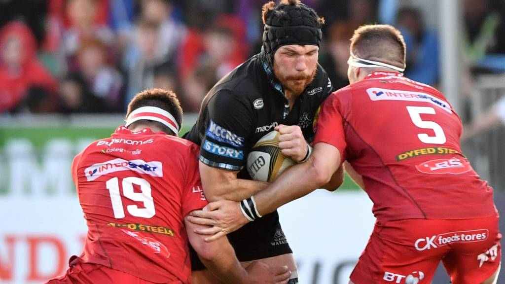 Glasgow Warriors' Tim Swinson makes is tackled by Scarlets' Steven Cummins (right) and Lewis Rawlins