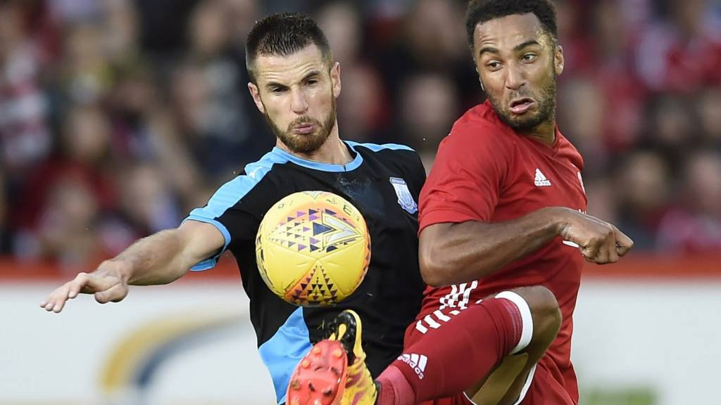 Apollon Limassol's Valentin Roberge in a challenge with Aberdeen's Nicky Maynard