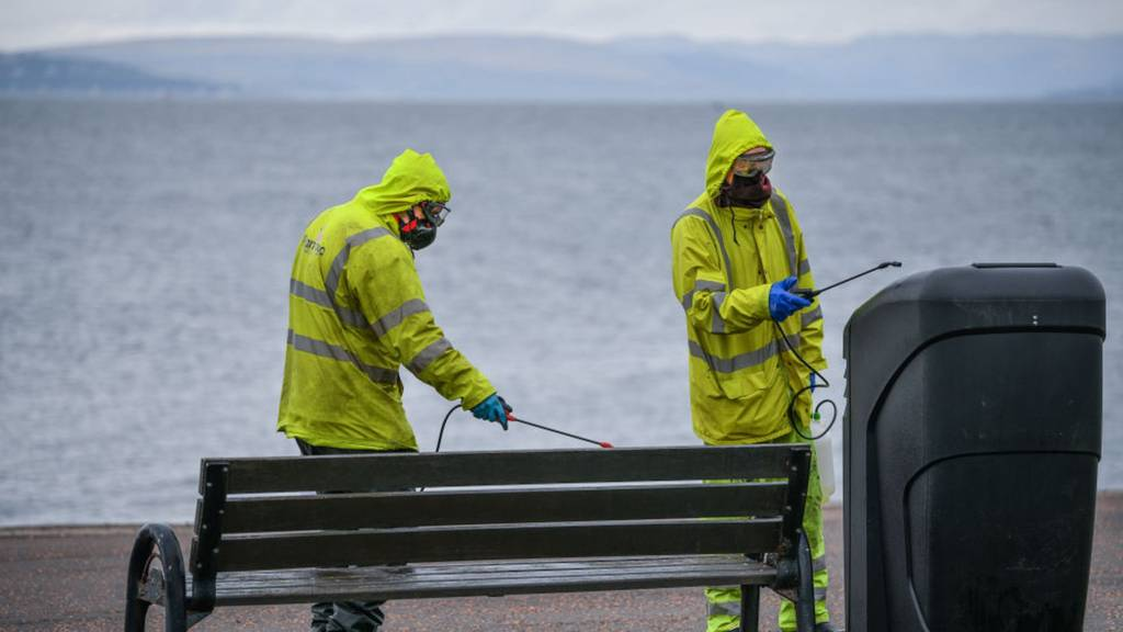council staff cleaning bench and bin